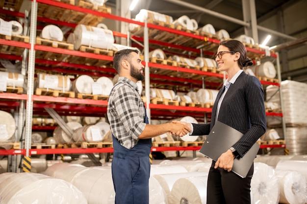 Dois parceiros de sucesso dando um aperto de mão no depósito de uma grande fábrica após negociação e fechamento de acordo
