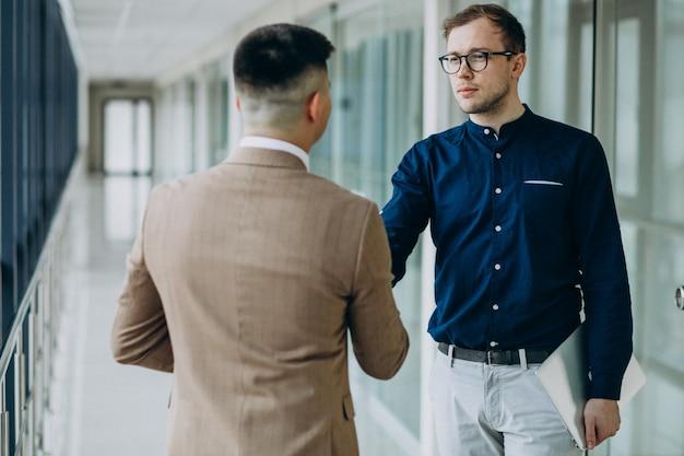 Dois parceiros masculinos, apertando as mãos no escritório