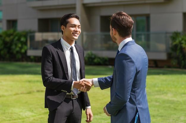 Dois parceiros sorridentes apertando as mãos ao ar livre