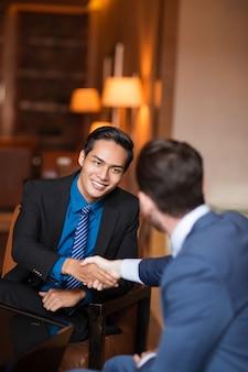 Dois parceiros sorridentes apertando as mãos no café