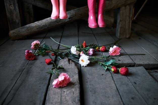 Dois pares de botas de borracha elegantes rosa cedendo piso de madeira e um grupo de flores frescas dentro de uma antiga casa de campo construída
