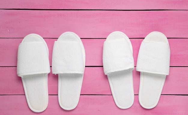 Dois pares de chinelos de hotel branco no chão de madeira rosa. vista do topo.