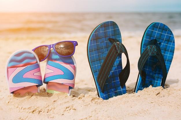 Dois pares de chinelos na areia na praia. óculos de sol em um deles. conceito de férias de verão. beira mar. paraíso.