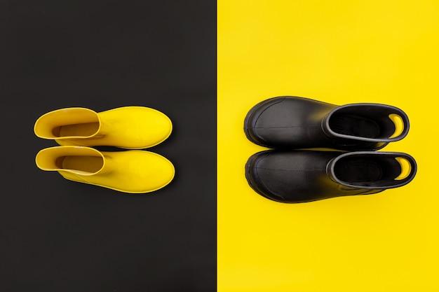 Dois pares de gumboots - macho amarelo feminino e preto - em pé opostos um ao outro nos fundos inversos.