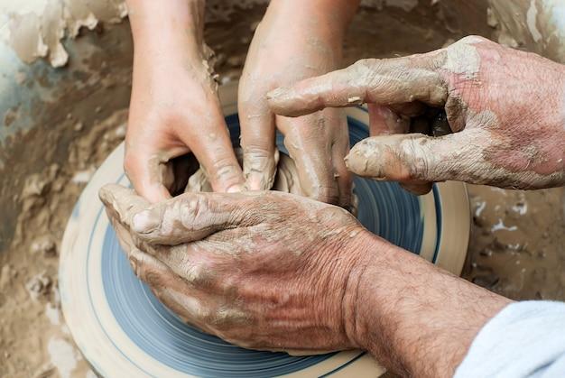 Dois pares de mãos - jovens e velhas - moldam algo de argila em uma roda de oleiro