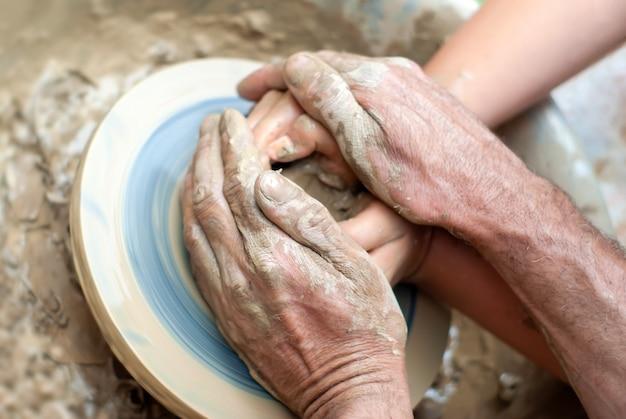 Dois pares de mãos - masculina e feminina, ou jovem e velha - criam um produto de argila na roda de oleiro