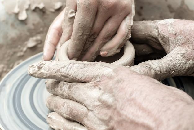 Dois pares de mãos masculinas e femininas moldam algo de argila em uma roda de oleiro