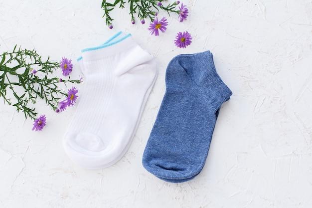Dois pares de meias femininas e flores no fundo branco estruturado, vista superior.