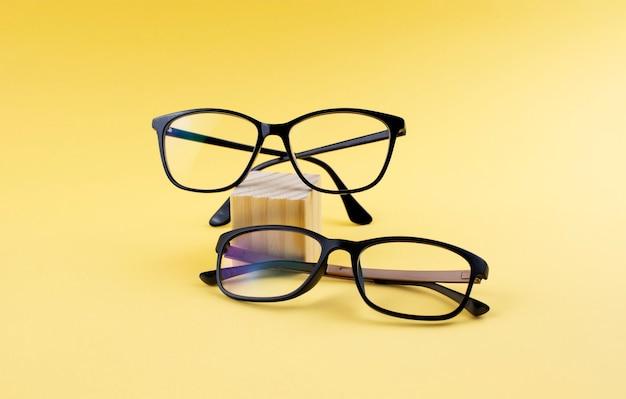 Dois pares de óculos pretos na superfície amarela