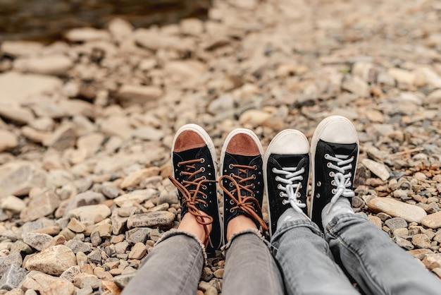 Dois pares de pernas em sapatos desportivos pretos apoiados em pedras ao ar livre
