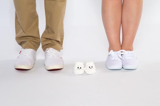 Dois pares de pés dos pais e sapatos de um bebê por nascer