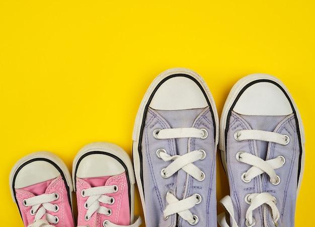 Dois pares de sapatos têxteis desgastados de diferentes tamanhos em um fundo amarelo