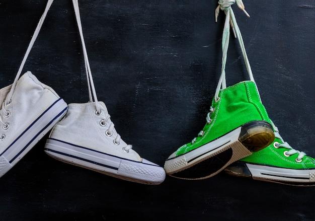Dois pares de sapatos têxteis usados pendurar em um fundo preto, close-up