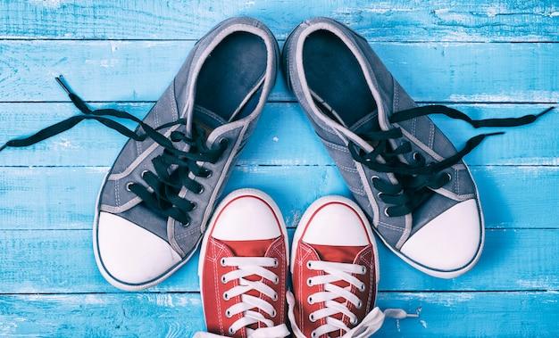 Dois pares de tênis têxteis com cadarços soltos estão em frente um do outro