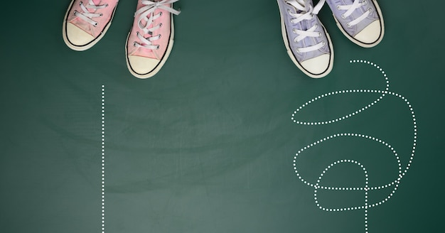 Dois pares de tênis têxteis em uma superfície verde. o conceito de escolher um caminho é difícil e confuso ou direto e fácil, vista de cima