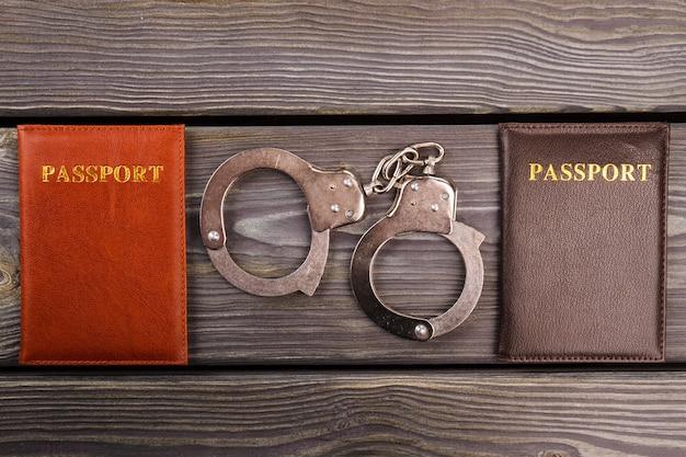 Dois passaportes e algemas. conceito de crime conjugal. fundo de madeira escura.