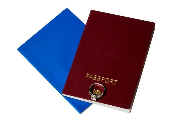 Dois passaportes em um deles um anel de noivado, uma imagem em um fundo branco