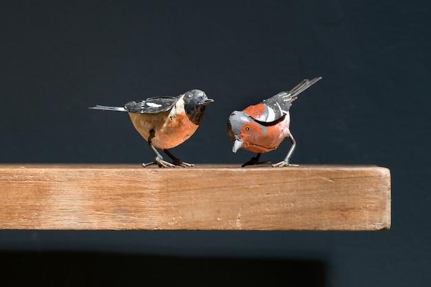 Dois pássaros de brinquedo de metal vintage em uma prateleira de madeira