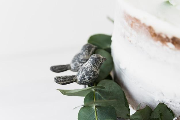 Dois pássaros perto do bolo branco e folhas no fundo branco