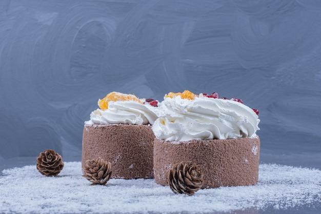 Dois pastéis cremosos com açúcar em pó e pinhas de natal
