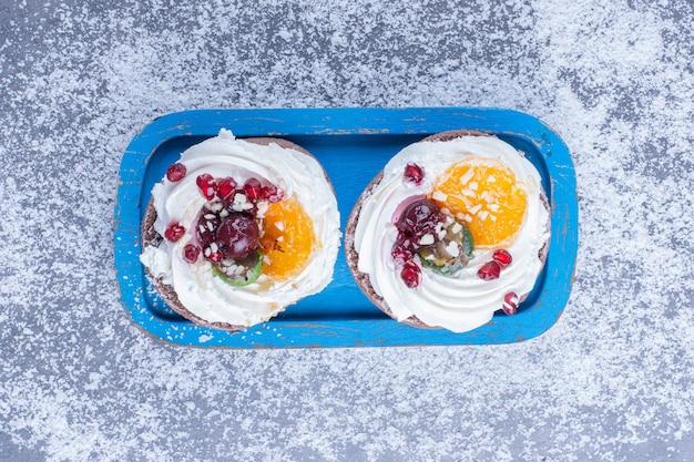Dois pastéis cremosos com açúcar em pó em um quadro azul