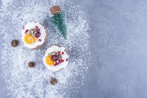 Dois pastéis cremosos com açúcar em pó em uma superfície cinza