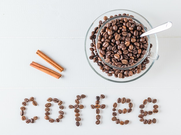 Dois paus de canela, uma xícara de café em grão e uma inscrição de feijão de café em uma mesa branca.