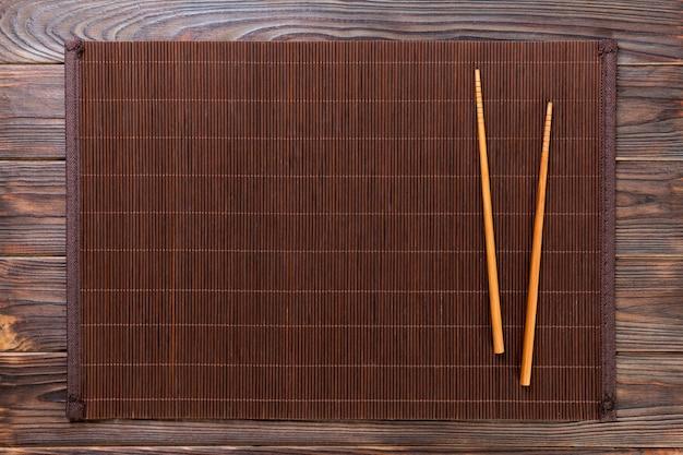 Dois pauzinhos de sushi com esteira de bambu vazia ou placa de madeira com fundo de madeira