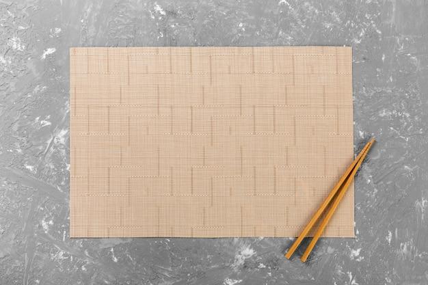 Dois pauzinhos de sushi com esteira de bambu vazia ou placa de madeira na parede de cimento vista superior com espaço de cópia. parede vazia de comida asiática
