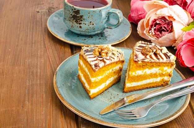 Dois pedaços de bolo de cenoura no prato azul, xícara de chá na mesa de madeira