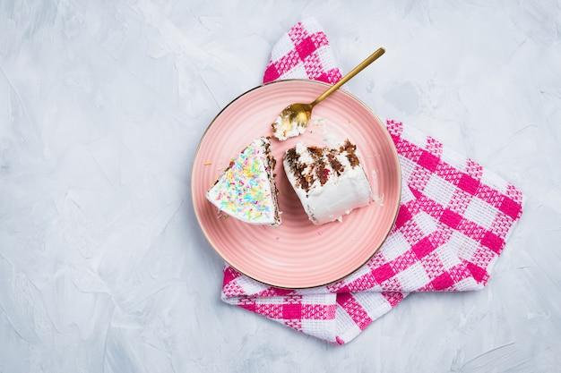 Dois pedaços de bolo de cenoura vegan com colher de ouro sobre fundo de cimento, flatlay
