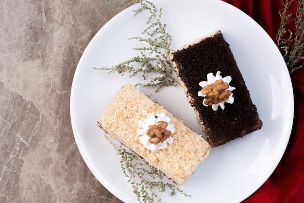 Dois pedaços de bolo em prato branco sobre superfície de mármore
