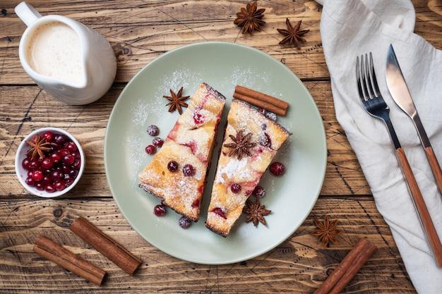 Dois pedaços de caçarola de torta de queijo cottage com amora bagas e especiarias canela e anis em um prato.
