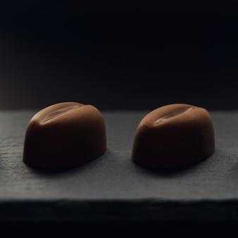 Dois pedaços de grãos de café em forma de chocolate no prato de pedra preto