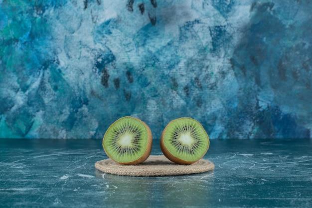 Dois pedaços de kiwi no tripé, sobre a mesa de mármore.