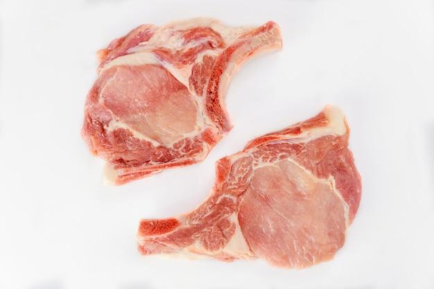 Dois pedaços de osso de costeleta de porco crua em isolado no fundo branco. vista do topo.