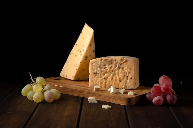 Dois pedaços de queijo granulado duro amarelo com nozes e uvas em uma tábua de cortar em uma parede preta