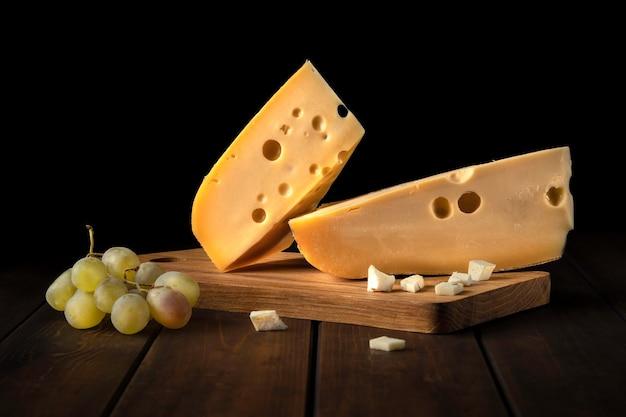 Dois pedaços de queijo suíço amarelo com buracos e um galho de uvas verdes em uma tábua contra uma parede preta