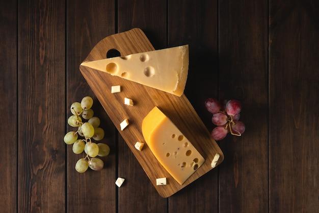 Dois pedaços de queijo suíço amarelo com buracos e um galho de uvas verdes em uma tábua, vista de cima