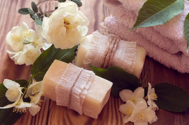 Dois pedaços de sabão branco seco com toalhas, rosas e jasmim