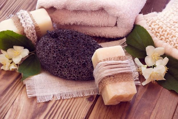 Dois pedaços de sabão seco com um jasmim, toalha, pedra-pomes e bast