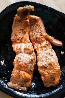 Dois pedaços de salmão grelhado em um prato preto