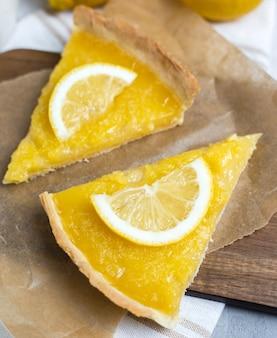 Dois pedaços de torta de limão com uma fatia de limão closeup, vista superior, copie o espaço.