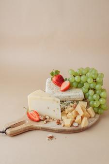 Dois pedaços grandes de banha de porco salgada e queijo saboroso com avelã, morango e uva no velho boardwall de madeira. estilo rústico. um delicioso lanche com bacon