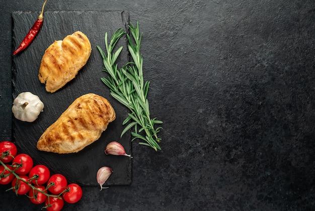 Dois peitos de frango grelhados em um fundo de pedra
