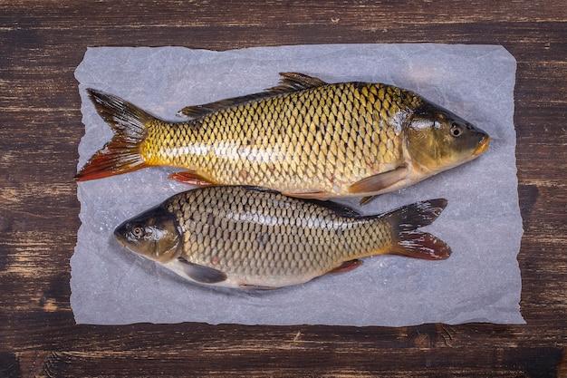 Dois peixes carpas no fundo de madeira, close-up, vista superior