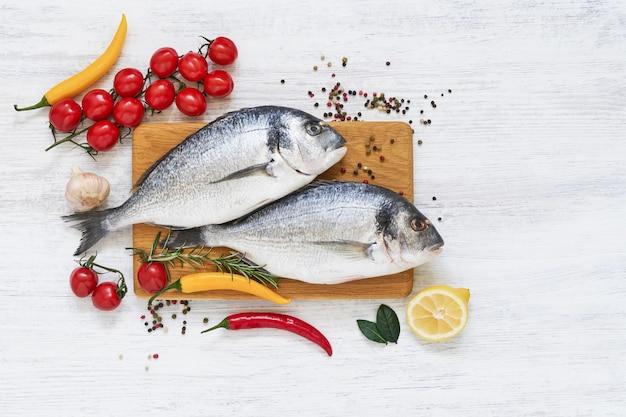 Dois peixes crus de dorada com legumes na tábua de madeira. conceito de comida saudável. vista superior, cópia