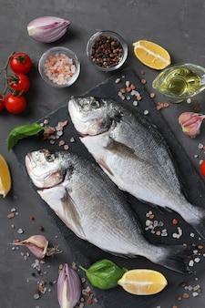 Dois peixes crus dourados com ingredientes e temperos como manjericão, limão, sal, pimenta, tomate cereja e azeite na mesa escura, vista superior. formato vertical