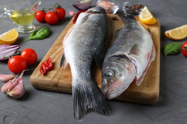 Dois peixes de robalo crus com ingredientes e temperos como manjericão, limão, sal, pimenta, tomate cereja e alho na placa de madeira