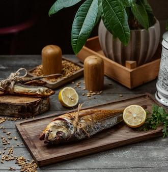 Dois peixes defumados secos, servidos na tábua de madeira com limão e salsa